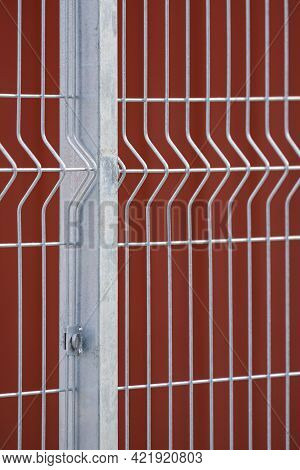 Focus At Prefabricated Fence Post And Grating Wire Panels With Blurred Red Steel Wall Background In