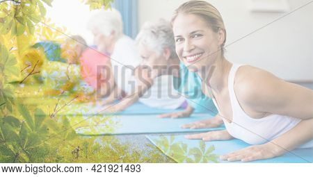 Composition of female instructor senior man and women exercising in fitness class with tree overlay. retirement, fitness and active lifestyle concept digitally generated image.