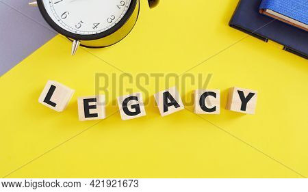 Legacy Word Made With Building Blocks, Yellow Background, Money Or Property Left To Someone Legacy C