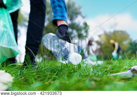 Hand Of Man Picking Up Bottle Into Garbage Bags While Cleaning Area In Park. Volunteering, Charity,