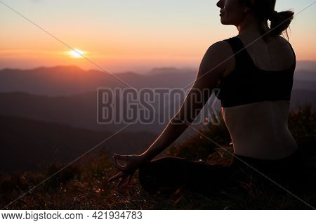 Cropped View Of Young Woman In Black Sportswear Doing Meditation At Sunset In The Mountains. Concept