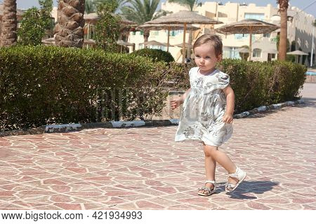 Little Girl Child With Serious Emotions In A Summer Dress On The Street On A Sunny Day, Vacation Wit