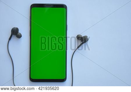High Angle Shot Of Smartphone Phone With Green Screen And Black Color Earphone On Top Of White Backg