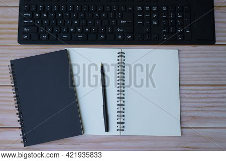 Homeoffice With Keyboard, Note Books And Pen On Wooden Table. Space For Text. Flat Lay, Top View