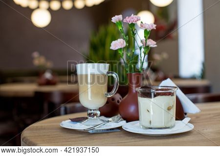 Tiramisu In A Transparent Glass, Lat, Pieces Of Dark Chocolate On A Wooden Table Against The Backgro
