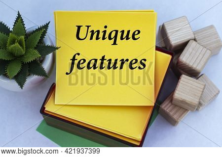 Unique Features - Words On A Yellow Note Paper On A Light Background With A Cactus