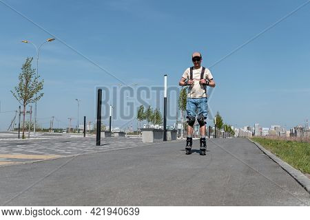 Young Man In Blue Shorts And Cap, In Protective Equipment Riding On Roller Skates On The Asphalt Roa