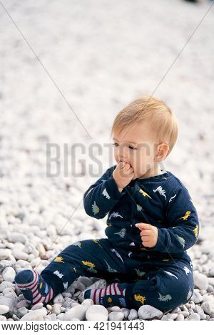 Cute Baby In Blue Overalls Sits On A Pebble Beach And Holds A Pebble In His Hand, Which He Puts In H