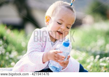 Smiling Little Girl With A Ponytail On Her Head Sits On A Green Lawn And Holds A Bottle In Her Hands