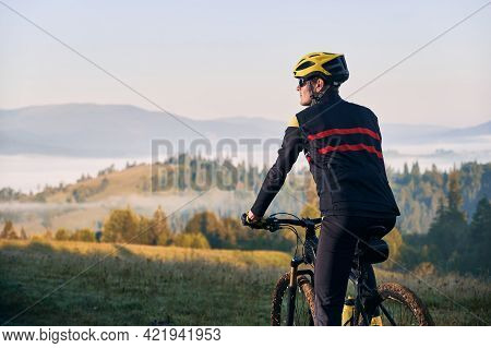 Close Up Male Cyclist In Cycling Suit Riding Bike With Hills On Background. Man Bicyclist Wearing Sa