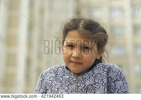 Girl 8 Year Old Against Buildings. Day, Horizontal Shot Front View.