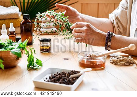 Woman Prepares Aromatherapy Session At The Table With Essential Oil Diffuser Medical Herbs, Differen