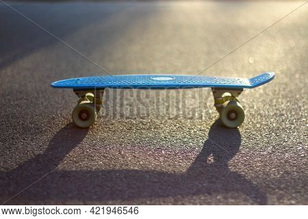 Defocus Close-up Blue Penny Board On The Asphalt Road In The Sunshine Outdoor. Blurred Bokeh. Mini C