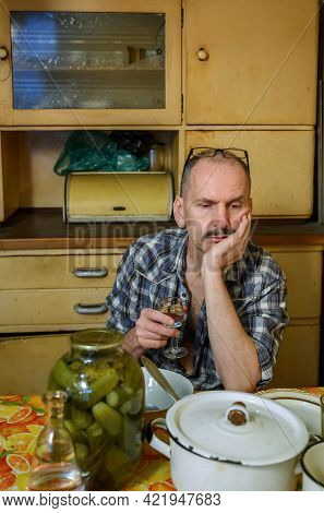Drunk Man Sitting In Kitchen At Home With A Glass Of Vodka In His Hand. Kitchen Utensils And A Jar O