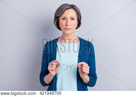 Photo Portrait Of Serious Senior Woman Keeping Glasses Wearing Blue Cardigan Isolated On Grey Color