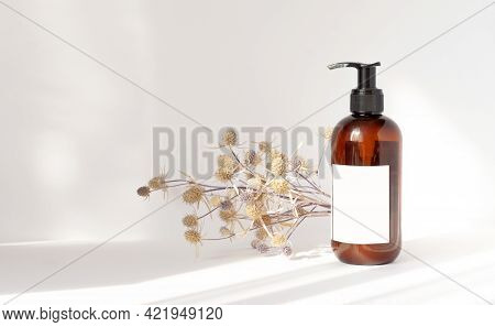 Brown Bottle With Dispenser And Empty White Label On Light Background. Next To Shampoo Package Is Bo