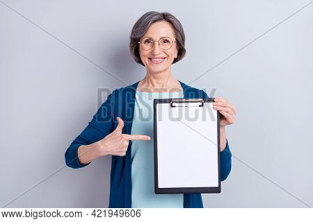 Photo Portrait Of Senior Business Woman Pointing Finger At Blank Space Keeping Clipboard Isolated On