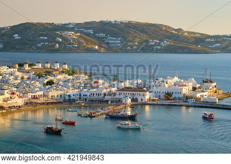 View of Mykonos town Greek tourist holiday vacation destination with famous windmills, and port with boats and yachtson sunset . Mykonos, Cyclades islands, Greece. With horizontal camera panning