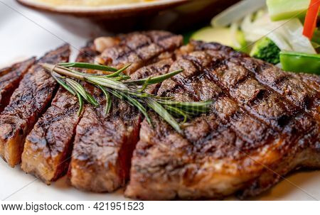 Close Up View On Serving Of Marinated Grilled Rib Eye Steak With Baked Potatoes And Vegetables.