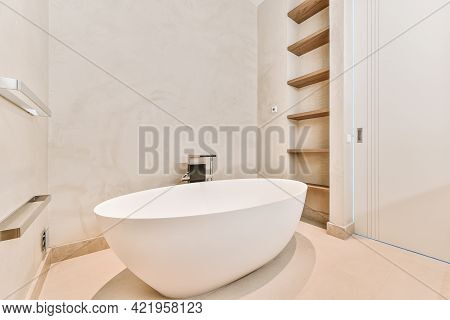 Minimalist Bathroom Interior Design With Big Soaking Tub In Center And Empty Shelves Built In Wall