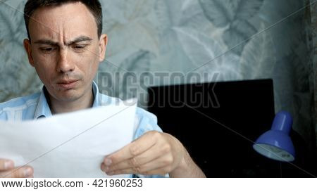 Frustrated Man Sitting At Desk With Paper Bills. He Feeling Stressed About Bank Loan Payment, Thinki