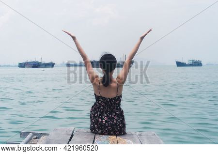 A Chinese Woman Sitting With Her Back To The Camera At The End Of The Historic Tan Jetty In The Geor