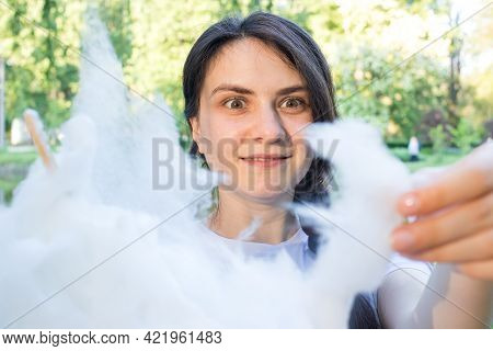 The Brunette Girl In Admiration Tears Off A Piece Of Cotton Candy. Delight And Happy Eyes From Sweet