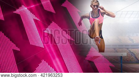 Composition of female athlete hurdle jumping with pink arrows and sport stadium. sports and competition concept digitally generated image.