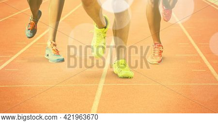 Composition of legs of athletes running on racing track with spots of light. sports and competition concept digitally generated image.