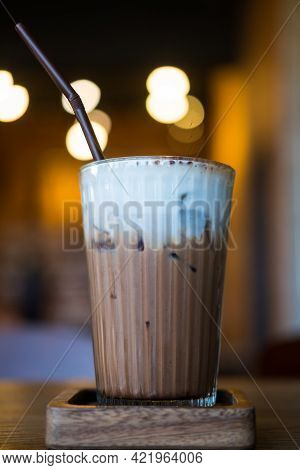 Iced Mocha With Milk Foam Placed On Wood Table And Against Bokeh Background