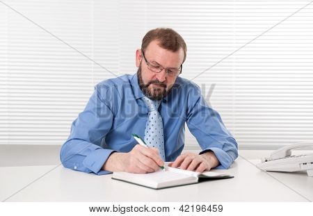 Businessman Makes A Note In Notebook