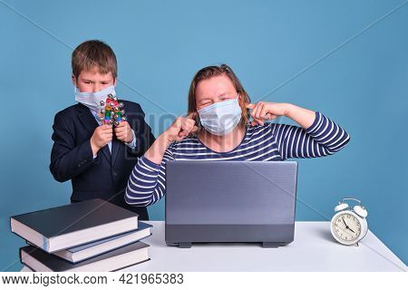 Junior Boy In A School Uniform Prevents His Mother From Working Remotely On A Laptop. Problems When