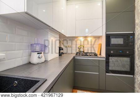 Well designed small dark grey modern kitchen interior