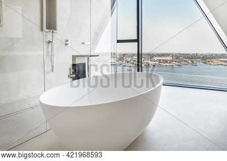 Big White Soaking Bathtub In Spacious Bathroom With Shower Cabin And Wall Window Viewing City