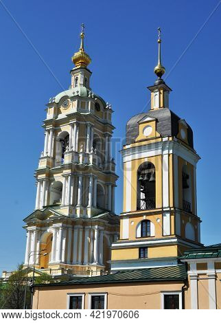 Two Bell Towers Against The Blue Sky. The Bell Tower With The Clock Of The Novospassky Monastery. Be