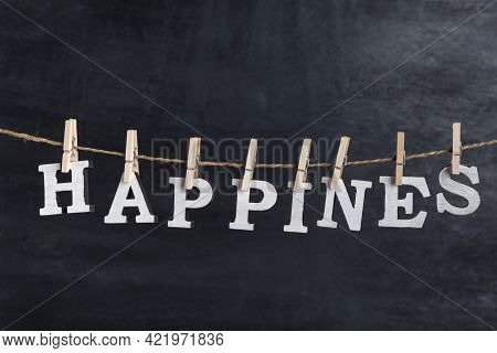 Word Happines Held On A Clothespin On A Rope Against Black Background. Inscription From White Letter