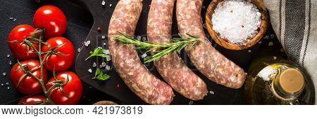 Bratwurst Or Sausages On Cutting Board With At Black Table.