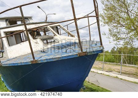 Abandoned Wrecked Boat Lying On The Shore, Waiting For Repairs, Fishing Boat.