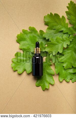 Bottle With Herb Essential Oil On Oak Background. Transparent Cosmetic Amber Glass Dropper Bottle, F