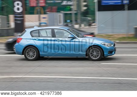 Moscow, Russia - April 2021: Side View Of Bmw 1 Series In Motion. Blue Hatchback Car Moving On The S