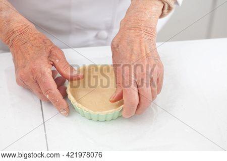 Senior Woman Preparing Dough For A Delicious Cheese And Ham Tartlet