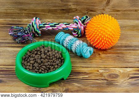 Dog Toys And Feed For Dogs In Green Plastic Bowl On Wooden Background. Dog Care Concept