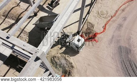 Beams With Steel Reinforcement. Dump Truck Unloads Sand In Construction. Aerial View. Unloading Soil