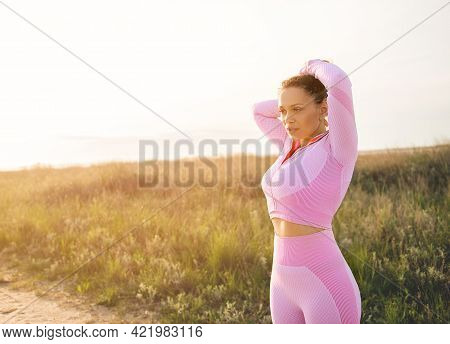 Young Sportswoman With Beautiful Aesthetic Body Ties Her Hair In A Ponytail Before Jogging Along A D
