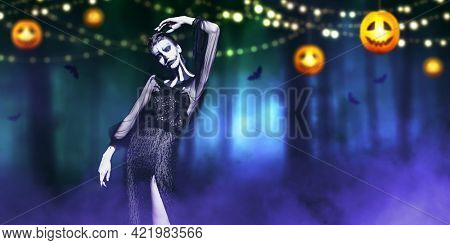 Beautiful graceful Pumpkin Queen stands against the backdrop of a dense forest with glowing pumpkin lanterns. Halloween. Day of The Dead.