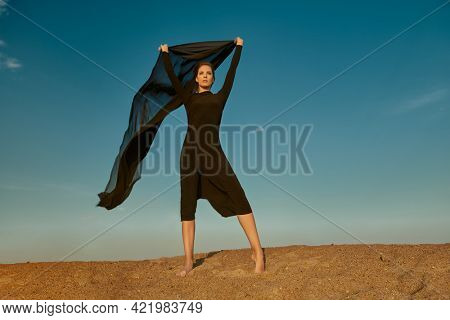 Fashion shot. Beautiful brunette woman in a long black dress posing in the desert with a scarf fluttering in the wind. Sky background.