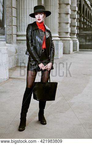 Attractive fashion model girl in leather jacket, shorts and leather boots over the knee and elegant hat poses on a city street. Fashion photo. Leather clothing style.