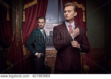 Men's beauty, fashion. Portrait of two handsome young men in elegant classic suits posing in a luxury apartments with classic interior.