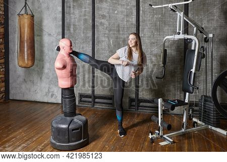 Punching Bag Bob Dummy In Gym, Young Woman Kicks.