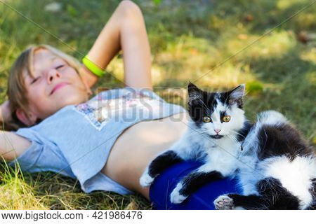 Defocus Blonde Little Girl Lying On Grass With Cat, Black And White Small Cute Kitten With Yellow Ey
